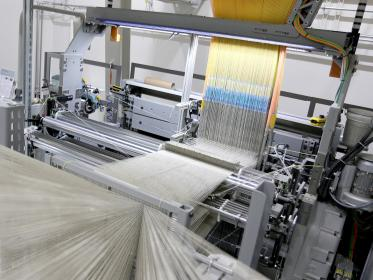 The Fraunhofer WKI double-rapier weaving machine with the Jacquard attachment in the upper of the photo.
